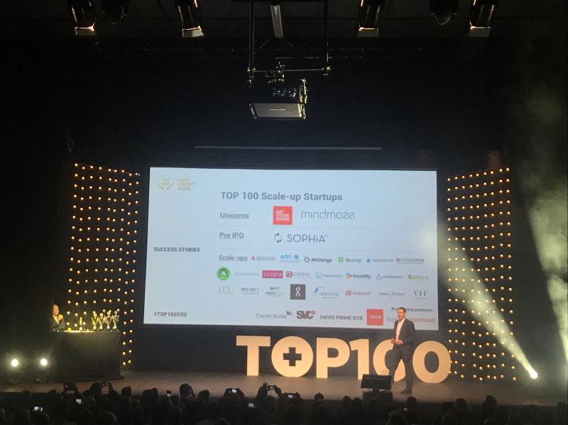 Man giving presentation in front of a audience at the TOP 100 event